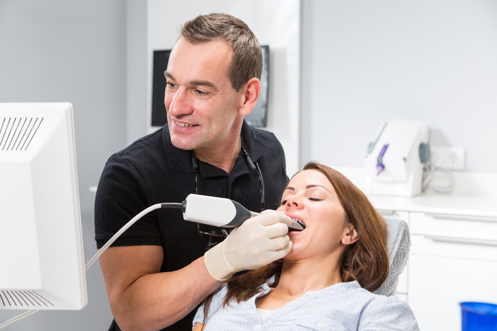 Dentist scanning patient's teeth with CEREC (Chairside Economical Restoration of Esthetic Ceramics) scanner