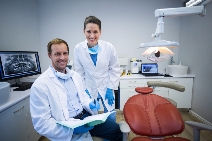 Portrait of smiling dentists holding medical report in dental clinic